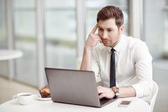 Przyjemny biznesmen pracuje na laptopie zdjęcia stock