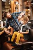 Przyjemny brodaty fryzjer męski robi jego pracie Fotografia Stock