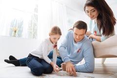 Przyjemny czułość ojciec robi z jego córką wyrzynarki łamigłówce fotografia royalty free