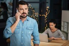 Przyjemny dobry przyglądający mężczyzna dyskutuje pracę na telefonie Obrazy Stock