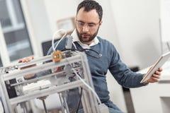 Przyjemny inżynier monitoruje pracę 3D drukarka w eyeglasses Zdjęcia Royalty Free