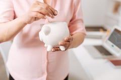 Przyjemny kobieta w ciąży trzyma prosiątko banka obrazy stock