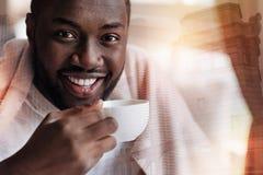 Przyjemny młodego człowieka uczucie relaksujący podczas gdy pijący herbaty obrazy stock