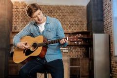 Przyjemny młody człowiek bawić się gitarę Zdjęcia Royalty Free