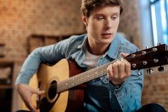 Przyjemny młody człowiek bawić się gitarę w domu Zdjęcie Stock