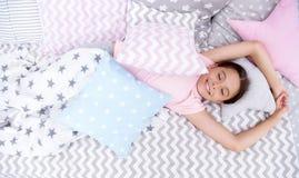 Przyjemny obudzenie Dziewczyny uśmiechnięty szczęśliwy dziecko kłaść na łóżku z gwiazdowego wzoru poduszkami i śliczną szkocką kr obrazy stock