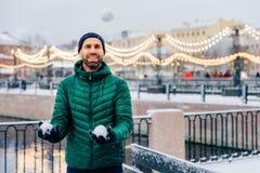Przyjemny przyglądający samiec model utrzymuje snowballs w rękach iść brzęczenia zdjęcia stock