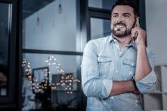 Przyjemny radosny mężczyzna ono uśmiecha się i komunikuje fotografia royalty free