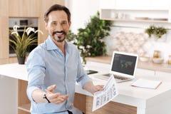 Przyjemny rozochocony mężczyzna trzyma wydruk zdjęcie royalty free