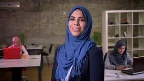 Przyjemny uśmiech arabska kobieta w błękitnej hijab pozycji po środku ceglanego biura relaksował z pracującymi dziewczynami