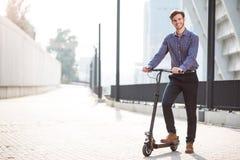 Przyjemny uśmiechnięty mężczyzna jedzie kopnięcie hulajnoga Obraz Stock