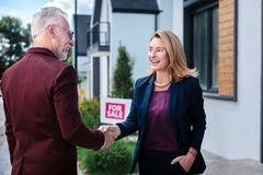 Przyjemny uśmiechnięty nieruchomość makler spotyka jej klienta kupienia luksusu dom zdjęcie stock