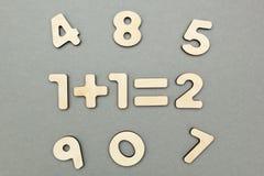 Przykład drewniane postacie: jeden plus jeden jest dwa na szarym tła tle zdjęcie royalty free