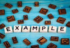 Przykładu słowo pisać na drewnianym bloku Drewniany abecadło na błękitnym tle Fotografia Royalty Free