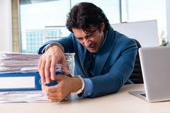 Przykuwający męski pracownik nieszczęśliwy z przesadną pracą zdjęcie stock