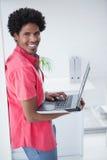 Przypadkowa biznesmen pozycja i używać laptop Obrazy Stock