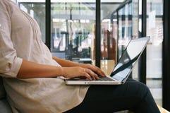 Przypadkowa biznesowa kobieta pracuje online na laptopie które wręczają na k Zdjęcie Royalty Free
