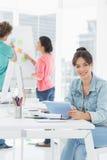 Przypadkowa kobieta używa cyfrową pastylkę z kolegami behind w biurze Obrazy Royalty Free