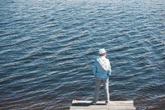 Przypadkowa mężczyzna pozycja na quay przed wody powierzchnią przy dniem Zdjęcia Stock