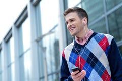 Przypadkowa mężczyzna przesłuchania muzyka na zewnątrz nowożytnego budynku Zdjęcia Royalty Free