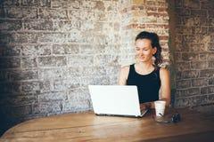 Przypadkowa młoda kobieta używa laptop dla dystansowej pracy przy sklep z kawą Obraz Royalty Free