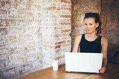 Przypadkowa młoda kobieta używa laptop dla dystansowej pracy przy sklep z kawą Portret atrakcyjna dziewczyna która komunikuje onl Zdjęcia Stock