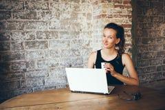 Przypadkowa młoda kobieta z ciemnym włosy używa laptop dla dystansowej pracy przy sklep z kawą Zdjęcie Stock