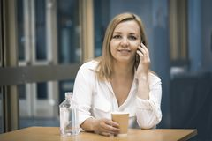 Przypadkowe kobiety używa mądrze telefonu i napoju kawę Fotografia Royalty Free