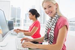 Przypadkowe młode kobiety używa komputery w biurze Zdjęcia Royalty Free