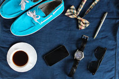 Przypadkowi błękitów buty z biel koronkami, pomarańczowy w kratkę bowtie, telefon, filiżanka herbata na zmroku - niebiescy dżinsy Zdjęcia Royalty Free