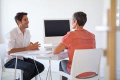 Przypadkowi ludzie biznesu opowiada przy biurkiem i ono uśmiecha się zdjęcia stock