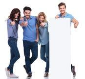 Przypadkowi przyjaciele przedstawia puste miejsce deskę i robi ok znakowi Zdjęcie Stock