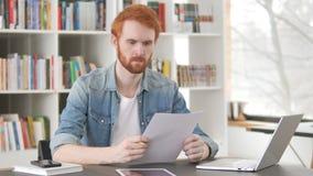 Przypadkowi rudzielec mężczyzny czytania dokumenty, kontrakt zbiory