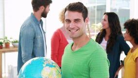 Przypadkowy biznesmen trzyma ziemną kulę ziemską z jego kolegami behind zdjęcie wideo