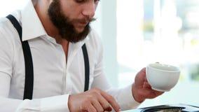 Przypadkowy biznesmen używa maszyna do pisania i pijący kawę zbiory