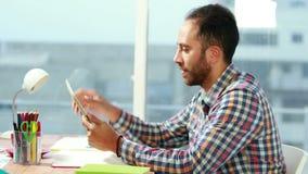 Przypadkowy biznesmen używa pastylkę przy biurkiem zbiory