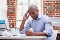 Przypadkowy biznesmena writing przy jego biurkiem Obrazy Stock