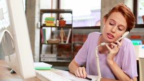 Przypadkowy bizneswoman na telefonie przy jej biurkiem zbiory