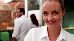 Przypadkowy bizneswoman ono uśmiecha się przy kamerą z drużyną za ona zbiory