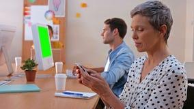 Przypadkowy bizneswoman texting podczas gdy jej koledzy pracuje na laptopie zbiory