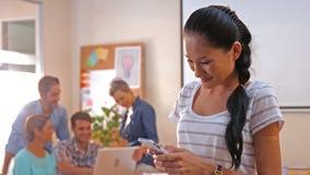 Przypadkowy bizneswoman texting z jej kolegami za ona zdjęcie wideo