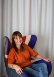 Przypadkowy eleganckiej kobiety obsiadanie w krześle przy biurem Zdjęcia Royalty Free