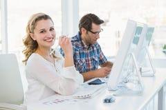 Przypadkowy fotografia redaktor pracuje przy biurkiem ono uśmiecha się przy kamerą Fotografia Stock