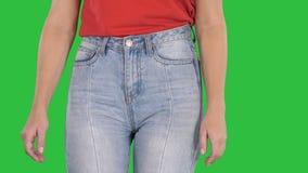 Przypadkowy kobiety odprowadzenie w wysokich cajgach i czerwona koszulka na zieleniejemy ekran, chroma klucz zbiory