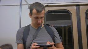 Przypadkowy mężczyzna use od telefonu komórkowego podczas gdy podróżujący na metrze Bezprzewodowy internet na transportu publiczn zbiory