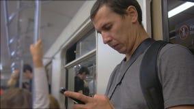 Przypadkowy mężczyzna use od telefonu komórkowego podczas gdy podróżujący na metrze Bezprzewodowy internet na transportu publiczn zbiory wideo