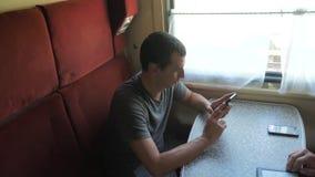 Przypadkowy mężczyzny czytanie od telefonu komórkowego ekranu podczas gdy czyta sms wiadomość podróżuje na taborowym furgonu styl zbiory