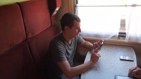 Przypadkowy mężczyzny czytanie od telefonu komórkowego ekranu podczas gdy czyta sms wiadomość podróżuje na taborowym furgonu styl zbiory wideo