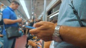 Przypadkowy mężczyzny czytanie od telefonu komórkowego smartphone ekranu podczas gdy spojrzenia nawigator podróżujący na metrze w zbiory wideo
