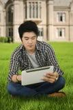 Przypadkowy męski uczeń z pastylką przy parkiem Zdjęcia Royalty Free
